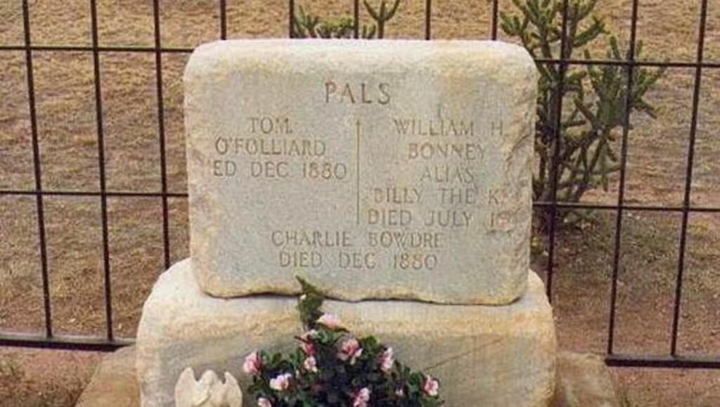 «KOMPISER»: Under gravoverskriften «kompiser», hviler Billy the Kid sammen med to andre lovløse på den gamle militærkirkegården i Fort Sumner. På gravsteinen fikk han navnet William H. Bonney, ett av flere navn han var kjent under i løpet av sitt korte liv. Etter å ha blitt stjålet flere ganger, står gravsteinen nå i et stålbur.Foto: Wikimedia commons