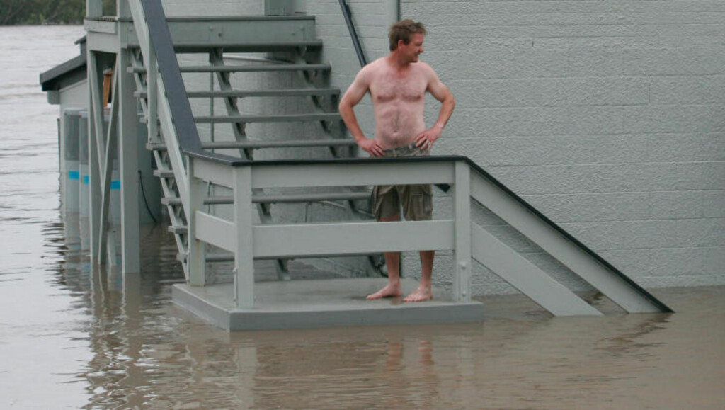 DÅRLIGE DAGER: Innehaver Brett Jensen ser vannmassene flomme forbi restauranten han driver i Bundaberg i Queensland, Australia. Foto: REUTERS