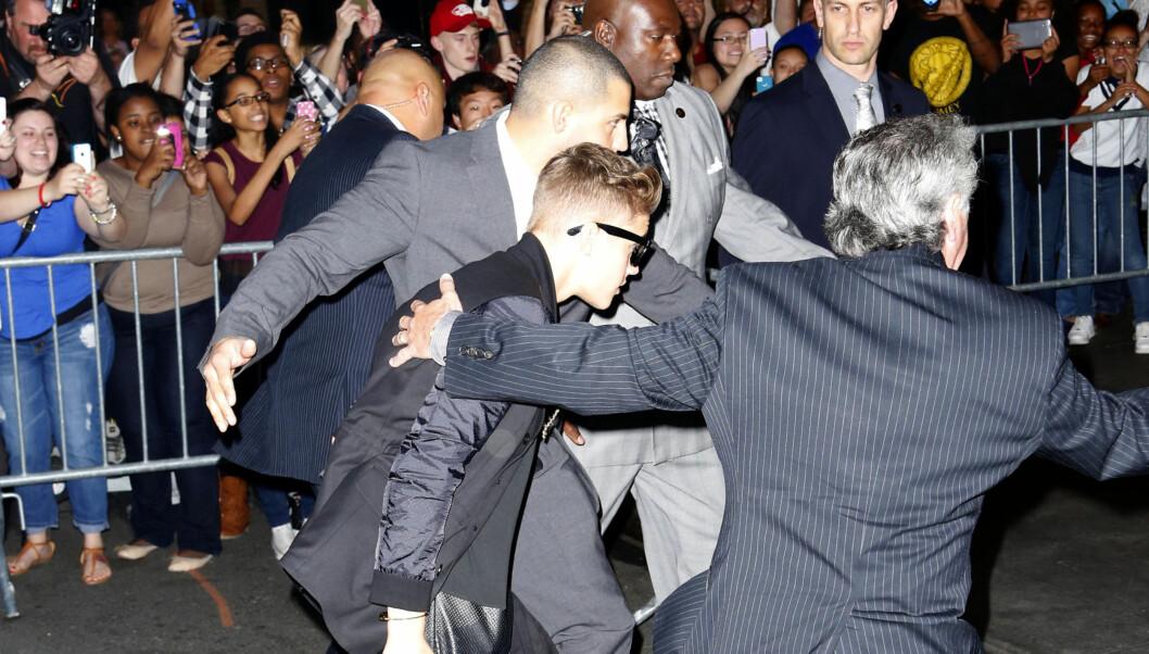 MÅ I RETTEN: Justin Biebers sikkerhetsvakter skal ha overfalt en paparazzifotograf som tok bilder av 19-åringen da han skatet på en parkeringsplass i Miami. Om det er de samme vaktene som på dette bildet, vites ikke. Foto: All Over Press