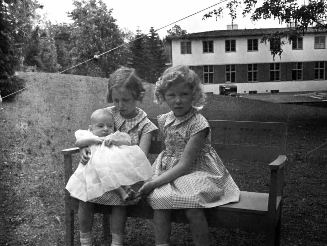 <strong>1937:</strong>  Prinsesse Ragnhild  (tv) og prinsesse Astrid med prins Harald, ca seks måneder gammel. De tre sammen, sittende på en benk i hagen.   Foto: SCANPIX