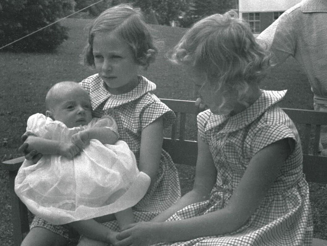 <strong>SKAUGUM 1937:</strong> Prinsesse Ragnhild  (tv) og prinsesse Astrid med prins Harald, her ca fire måneder gammel. De tre sammen, sittende på en benk i hagen.  Foto: SCANPIX