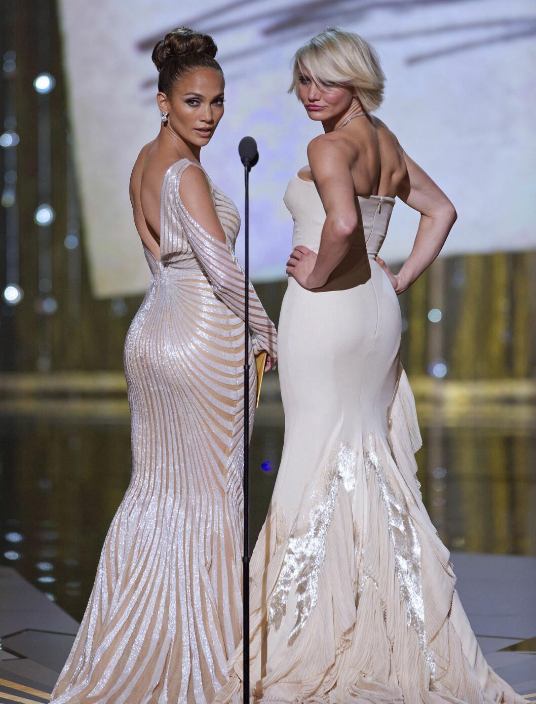 SNUR GJERNE RYGGEN - TIL PUBLIKUM: Her viser Jennifer Lopez og Cameron Diaz fram bakdelen til publikum under Oscar-utdelingen. Begge iført kremhvite kjoler.  Foto: Fame Flynet