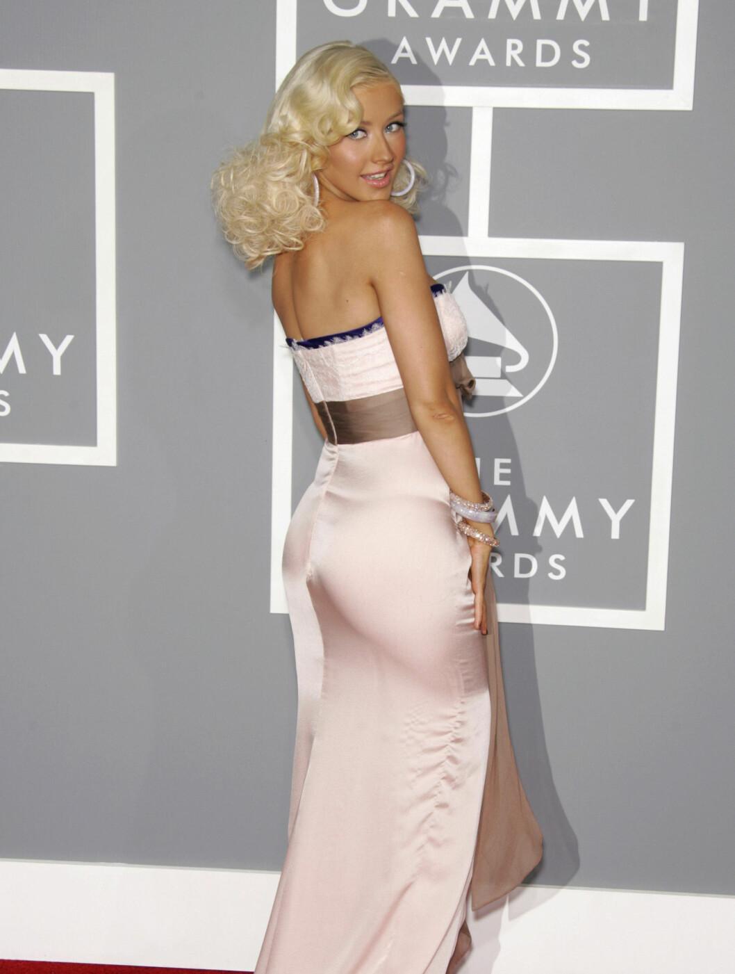 SKINNENDE BLANK ROMPE: Her bruker Christina Aguilera en lys rosa silkekjole. Den skinner i blitzen fra fotografene, som snudde rumpa til på Grammy Awards i 2007. Foto: Fame Flynet