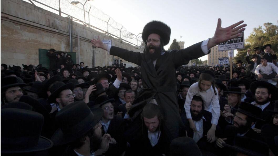 <strong>HEIES FRAM:</strong> En far blir båret inn i fengsel av støttespillere. 100 000 ultraortodokse jøder demonstrerte i Jerusalem i dag mot at deres barn skal gå i klasse med andre jøder. Foto: AFP