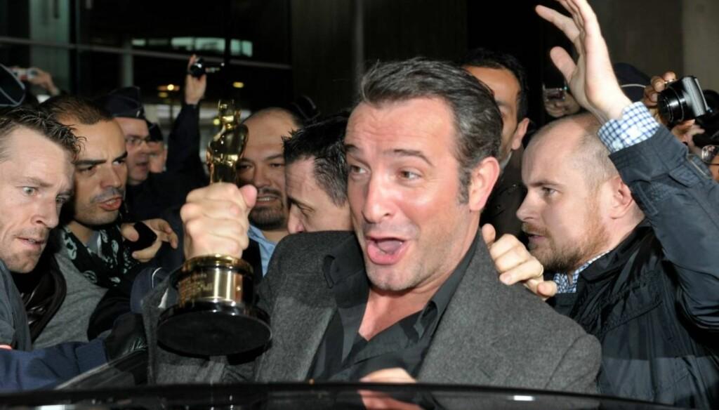 OMSVERMET: Jean Dujardin ble mottatt som en helt da han landet i Frankrike etter å ha vunnet prisen for beste mannlige skuespiller under Oscar-utdelingen.   Foto: Stella Pictures