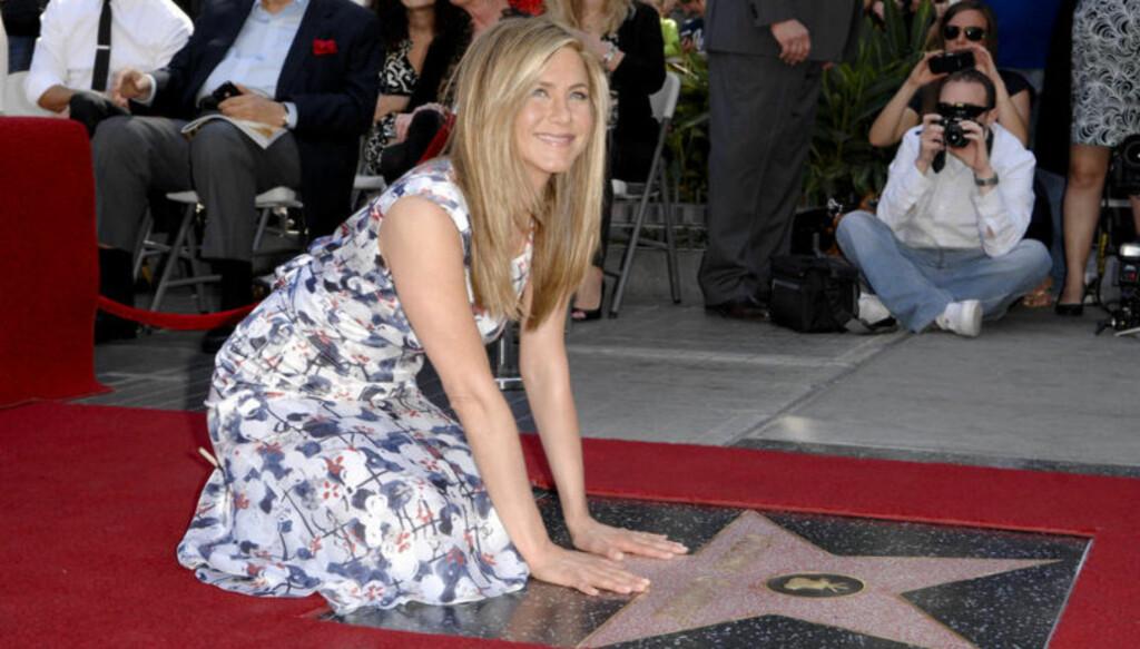 NED PÅ KNE: Slik så det ut da Jennifer Aniston tidligere i februar ble hedret med sin egen stjerne på Hollywoods Walk of Fame. Foto: Fame Flynet
