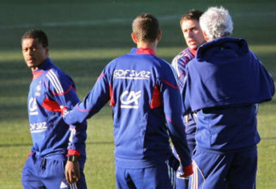 <strong>HÅNDGEMENG:</strong> Patrice Evra knuffet med Frankrikes fysiske trener, Robert Duverne. Raymond Domenech kom mellom. Foto: Franck Fife / AFP.