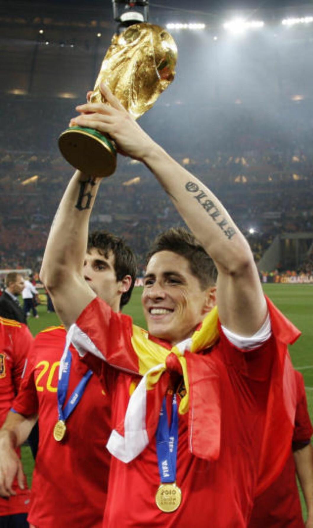 <strong>MED SPANSK FLAGG:</strong> Fernando Torres tok turen opp til Fifa-presidenten for å hente medaljen. Her løfter han pokalen ute på banen. Foto: AP/Bernat Armangue