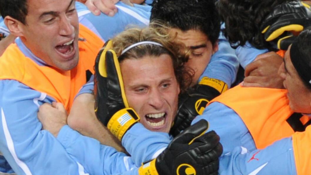 <strong>VM-HELT:</strong> Diego Forlan ble kåret til VMs beste spiller etter nesten egenhendig å ha tatt Uruguay til semifinale. Lagkameratene feiret superspissen med å kaste ham ut i svømmebassenget på spillerhotellet.Foto: SCANPIX
