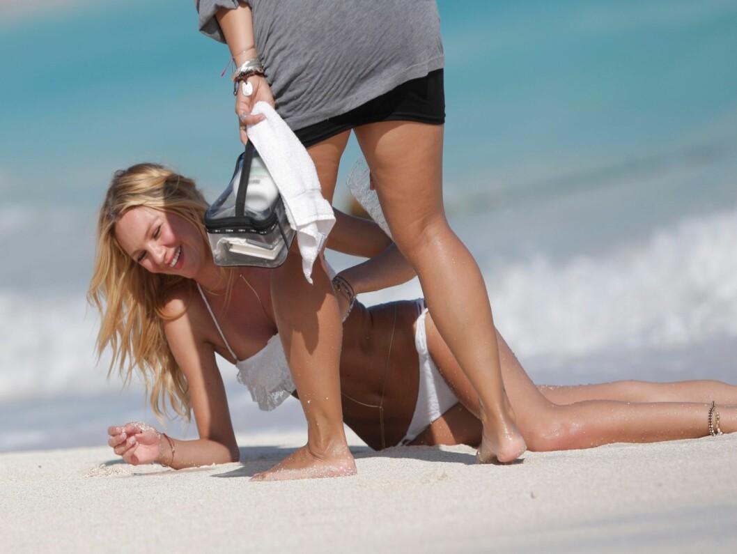 OOOPS: Candice Swanepoels bikini holdt flere ganger på å dette ned under fotoshooten på St. Bart, men med hjelp fra stylisten fikk hun klærne under kontroll. Foto: Stella Pictures