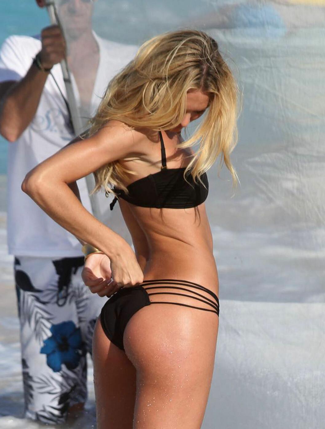 EN HJELPENDE HÅND: Candice sjekker at bikinien sitter som den skal. Foto: Stella Pictures