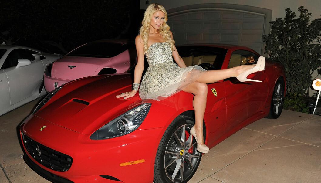 SEXY POSERING: Paris Hilton tok imot kjendisgjestene mens hun satt på sin nye røde Ferrari i innkjørselen til luksushjemmet i Beverly Hills.  Foto: All Over Press