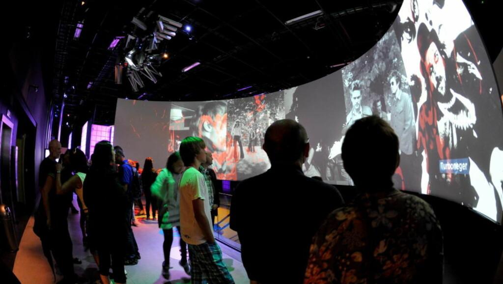 SKJERMER: For de fleste besøkende vil møtet med hvert tiår siden 50-tallet på hver sin storskjerm være introduksjonen til Rockheims vidunderlige verden. Fra punkter i gulvet kan publikum ved hjelp av armbevegelser og peking styre innholdet på skjermene. Foto: Ned Alley / Scanpix