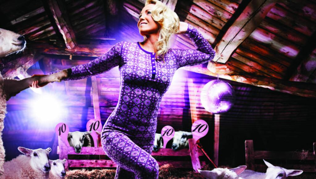 SAUE-DOMMERE: På Kari Traas reklamekampanje for sitt eget ullundertøy, danser hun med en sau på en låve mens et dommerpanel bestående av fire sauer gir henne sine høyeste poeng. - Det er ikke ment som å fremstille dommerne som sauer, sier hun til S Foto: Kari Traa