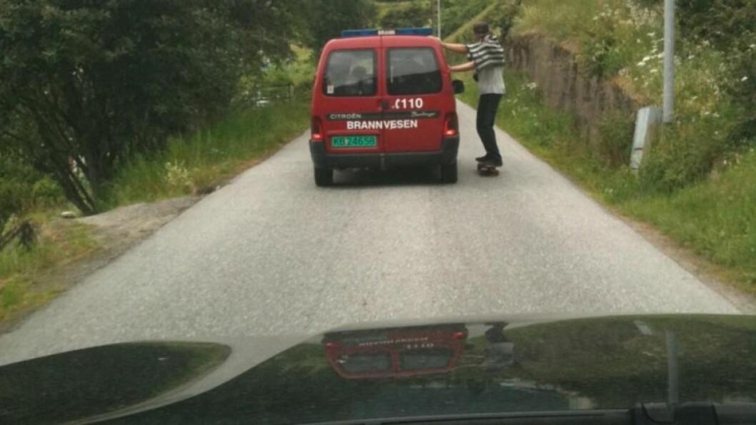 <strong>HAIK:</strong> Mannen på rullebrett holder fast i brannbilen. Foto: Nanje Leikanger