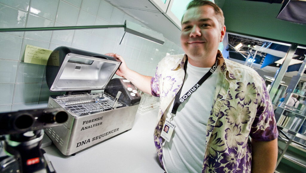 AVSLØRER SANNHETEN: Selv blant det dataskjermene og det autentiske labutstyret i studioet til «Spesialenheten», er ikke alt slik det ser ut på TV i TV3-serien. Her viser skuespiller Nils Jørgen Kaalstad fram en DNA-analyse maskin, som egentlig er en  Foto: Per Ervland, Seher.no
