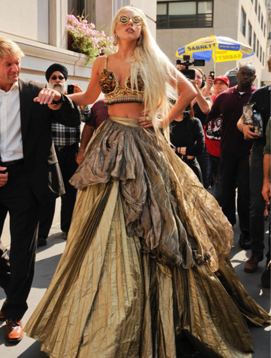 <strong>FIKK EN HÅND:</strong> Lady Gaga forsøker å posere mens hun støtter seg til en av livvaktene sine. Foto: All Over Press