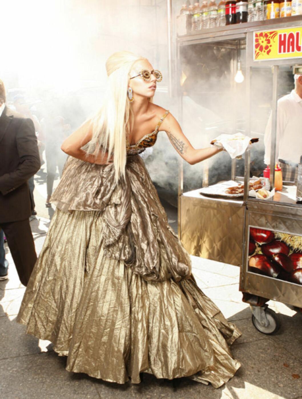 <strong>STILIG:</strong> Umulige antrekk kombinert med unaturlige positurer? Motereportasje i Vanity Fair, så klart! Lady Gaga «spiser» pølse i brød under fotograferingen. Foto: All Over Press