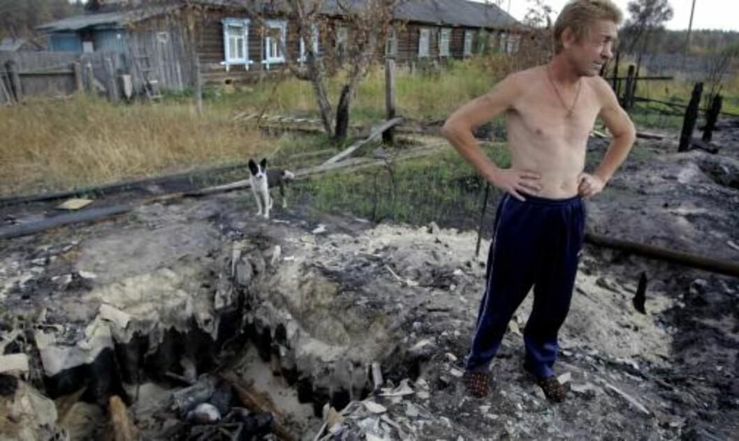 <strong>MISTA HUSET:</strong> Andrej Saveljev (46) står ved restene av huset sitt, som ble brent ned under skogbrannene i landsbyen Juznij, øst for Moskva. Foto: AP/Sergej Ponomarev).