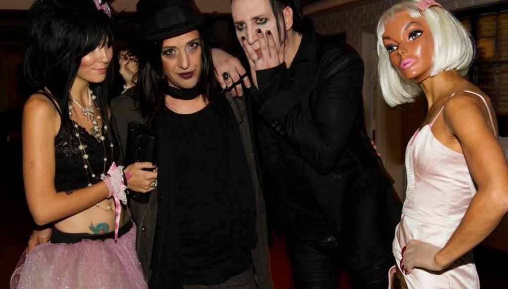 NY KJÆRESTE?: Det spekuleres i om den maskekledte kvinnen er Mansons nye kjæreste. Hun sjokkerte fotografene ved å stille i en lyserosa kjole som var helt åpen i skrittet. Foto: All Over Press