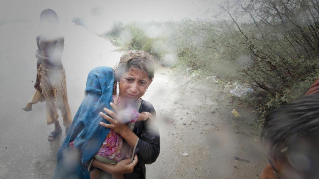 <strong>PÅ FLUKT:</strong> En jente i Punjabi-provinsen med en liten søster på armen gråter etter å ha blitt robbet for risen hun hadde fått. Hun er en av flere millioner som er på flukt som følge av flomkatastrofen i Pakistan. Foto: REUTERS/Adrees Latif/ SCANPIX.