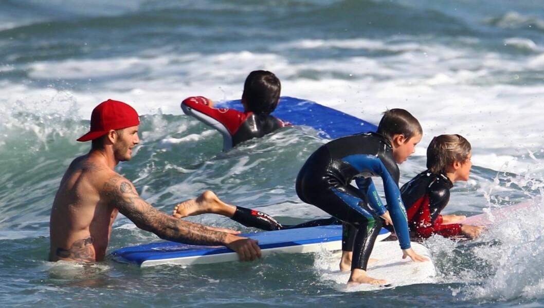 <strong>PÅ BØLJAN BLÅ:</strong> David Beckham gir sønnene et dytt i riktig retning under surfeturen søndag. Foto: All Over Press