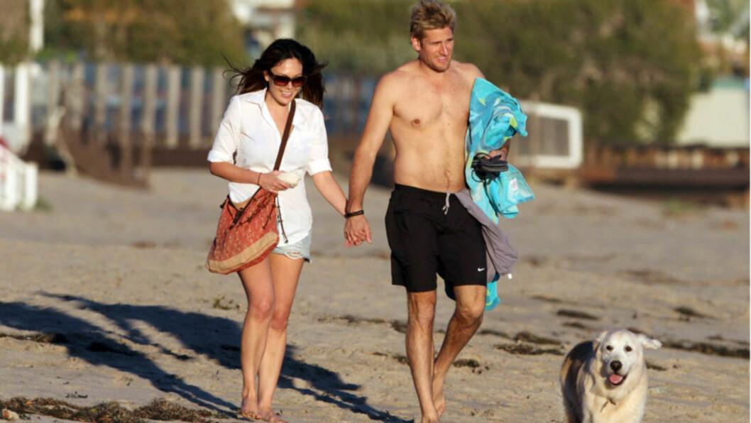 FAMILIEFORØKELSE: Skuespiller Lindsay Price og kjendiskokk Curtis Stone har allerede hus og hund (t.h) i boks, så da er vel barn det neste naturlige skrittet - nå venter de i hvert fall sitt første barn sammen. Her koser de seg på stranden i Malibu i Foto: All Over Press
