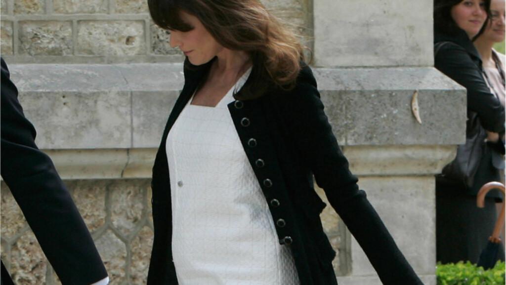 GOD MAGEFØLELSE: Frankrikes presidentfrue Carla Bruni ser ut til å endelig komme graviditetsryktene i møte. Under G8-møtet torsdag var hun nemlig iført en kjole som bekreftet de fleste rykter... Foto: All Over Press