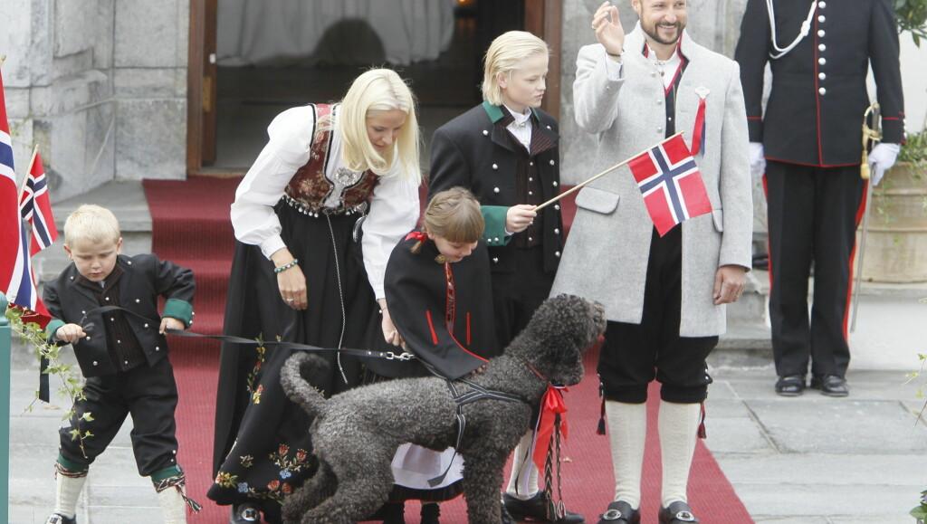 NYSGJERRIG HUND: Prins Sverre Magnus og prinsesse Ingrid Alexandra hadde sin fulle hyre med å få hunden Mily Kakao til å sitte i ro på Skaugum-trappa, da kronprinsfamilien møtte folket på morgenen 17. mai. Foto: Scanpix