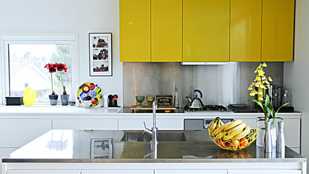 <strong>Bryter normen:</strong> Nordmenn flest har hvitt kjøkken. Det har Tuva Voll og familien også, men med overskap som tydelig skiller seg fra det tradisjonelle. Gule detaljer går igjen på resten av kjøkkenet. Foto: Anniken Zahl Furunes.