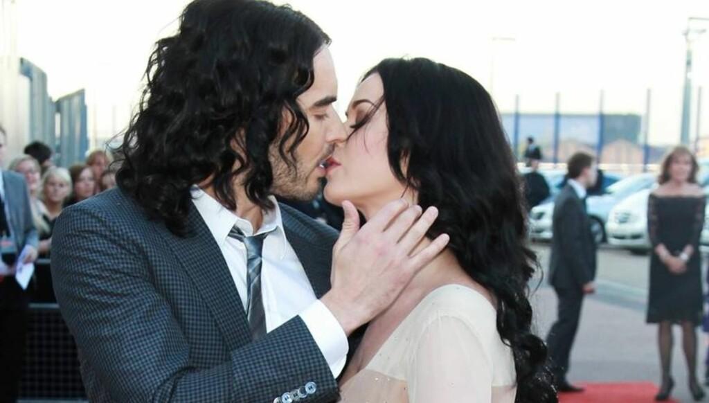 HETT KYSS: Russell Brand nølte ikke med å kysse sin kone Katy Perry foran fotografene før premieren på filmen «Arthur» i London tirsdag. Foto: All Over Press