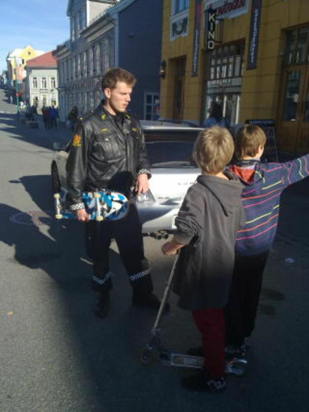<strong>TRUENDE:</strong> Politimann Per Arne Juvang snakker med noen gutter som har vært vitne til hendelsen. Foto: Guttorm Pedersen/Nordlys