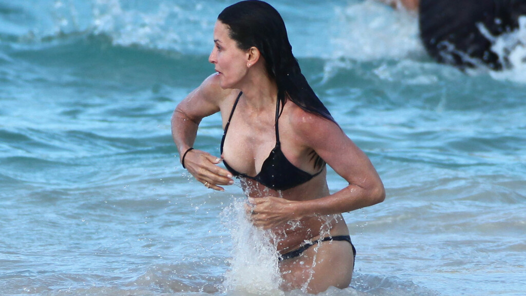 PUPPEGLIPP: Courteney Cox viser litt for mye på stranden i St. Barts.  Foto: All Over Press