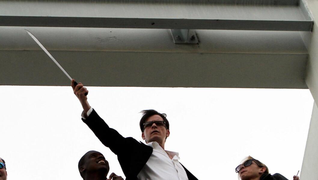 SJOKKERER IGJEN: Charlie Sheen dukket tirsdag opp på et tak i Beverly Hills med en diger machete. Til høyre står en av Sheens to kjærester, Natalie Kenly.   Foto: All Over Press