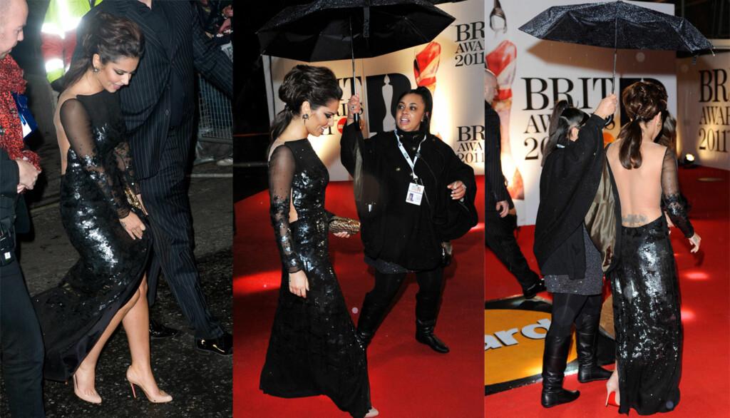 REGNTRØBBEL: Cheryl Cole smilte tappert mens regnet høljet ned over hodet hennes på den røde løperen.  Foto: All over press