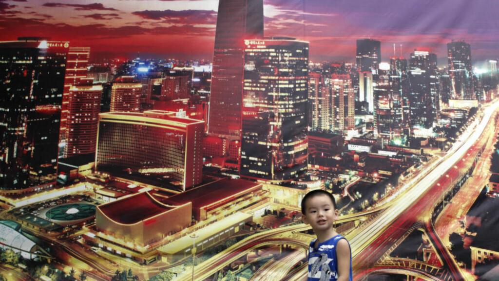 VOLDSOM VEKST: En gutt passerer bildet av Beijings forretningsdistrikt. Jeg tror vi kommer lengst med å vise respekt for hva Kina har oppnådd, skriver Raymond Johansen. Foto: Reuters/Scanpix