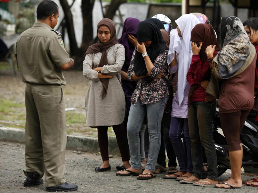 """SHARIAPOLITIET: Her får unge jenter i Banda Aceh """"råd"""" under en gateinspeksjon av en shariapolitimann. Buksene er etter politimannens syn for trange og korte. Foreløpig er Aceh dem eneste provinsen i Indonesia som har innført lovlige shariadomstoler. Foto: REUTERS/Beawiharta"""
