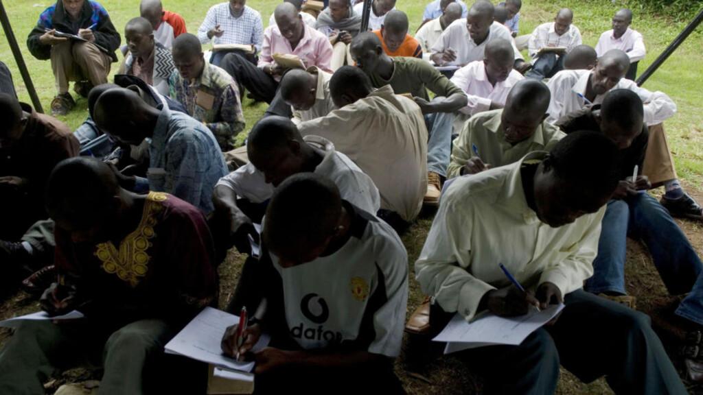 HÅPEFULLE: Et titalls ugandiske unge menn signerer kontrakt med Dreshak International, et av de to rekrutteringsselskapene som sender leiesoldater fra Kampala til Irak. Foto: AFP/Walter ASTRADA