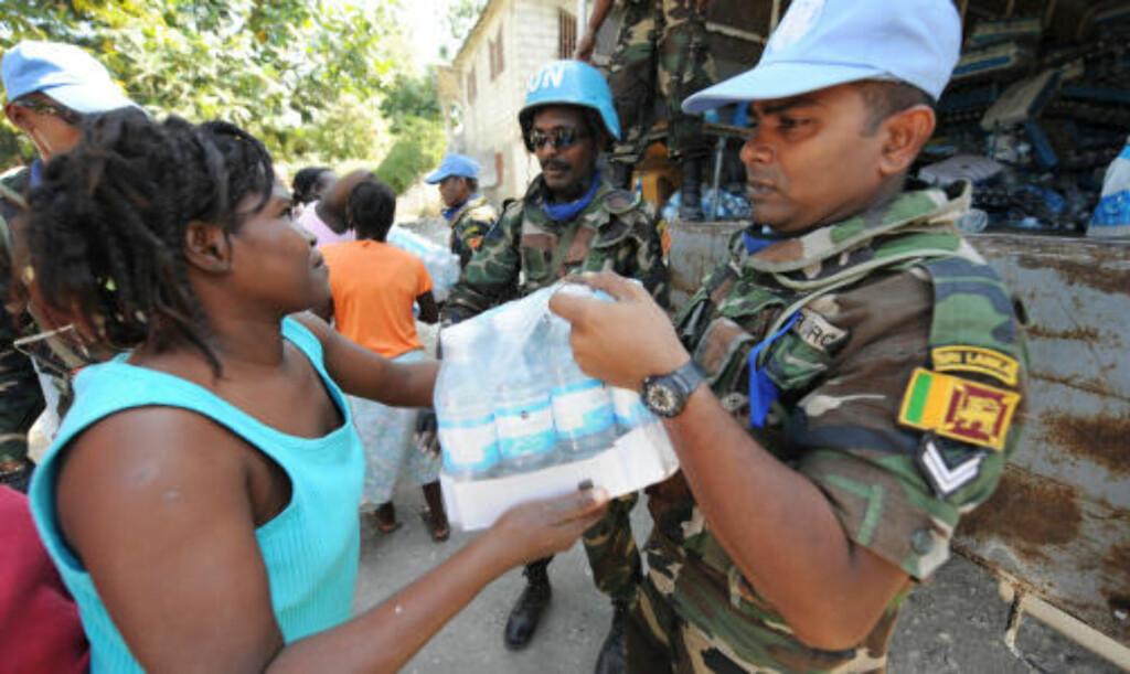 FÅR MAT OG DRIKKE: FN mener det gir best resultater hvis matrasjonene deles ut til kvinner. Foto: AFP PHOTO/Stan Honda/Scanpix