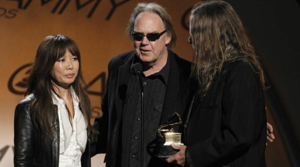 PÅ HØY TID: Først etter at han oppsummerte karrieren med påkostet bokssett, ble Neil Young tilgodesett med Grammy-pris. Her takker han for den sammen med boksdesignerne Jenice Heo og Gary Burden. Foto: SCANPIX/AP Photo/Matt Sayles