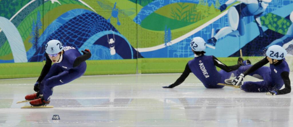 VANT OG FALT:Lee Jung-su går inn til OL-gull på 1500 meter skøyter kortbane mens hans to lagkamerater har falt slik at Sør-Koreas trippelseier glapp. (Foto: Andy Clark, SCANPIX/Reuters)