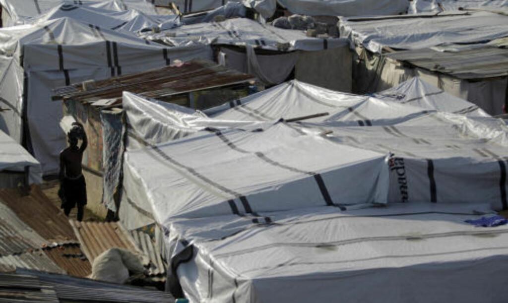 EN MILLION HUSLØSE: En mann vandrer gjennom en flyktningleir i byen Leogane i Haiti. En million mennesker er husløse etter jordskjelvet som rammet landet for en drøy måned siden. En konferanse om gjenoppbyggingsarbeidet er nå utsatt til begynnelsen av juni. Foto: SCANPIX/REUTERS/