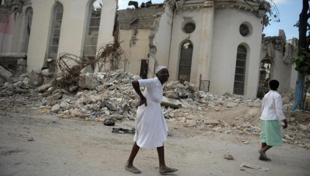 MÅ VENTE: En eldre kvinne spaserer foran ruinene av katedralen i Port-au-Prince etter en utendørs messe i Haitis hovedstad. Konferansen om gjenoppbygningen av landet er nå utsatt, og det kan bli lenge til innbyggerne får en ny katedral å holde messe i. Foto: AFP/Eitan Abramovich
