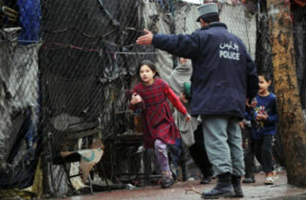 ADVART: En afghansk jente blir dirigert av en politimann. Over høytalere ble Kabuls innbyggere bedt om å holde seg innendørs etter selvmordsangrepet. Foto: AFP PHOTO/Massoud HOSSAINI/SCANPIX