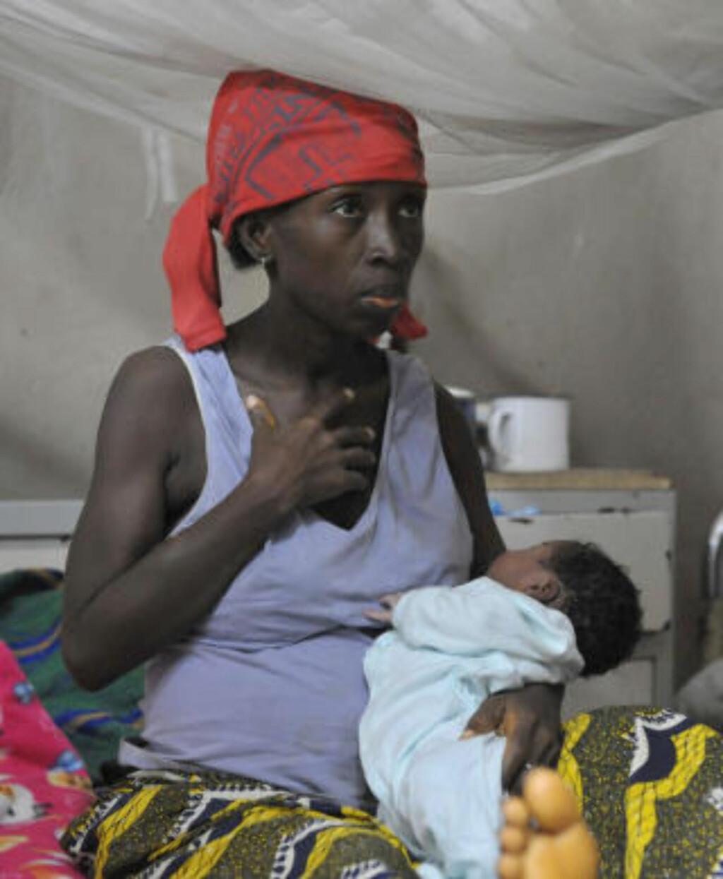 SIERRA LEONE: En kvinne holder en baby på et sykehus i Freetown i Sierra Leone. I landet dør hver åttende gravide kvinne i forbindelse med svangerskap eller fødsel, og av 1000 fødte babyer dør 282 i løpet av de første fem leveårene. Kun 24 % av kvinnene kan lese og skrive. Sierra Leone regnes av CARE som verdens fjerde verste land for kvinner. Foto: AFP PHOTO / ISSOUF SANOGO / SCANPIX