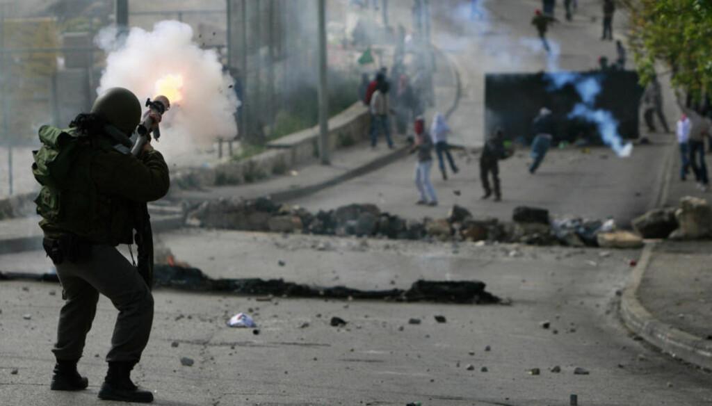 SKYTER TÅREGASS: En israelsk grensepolitimann skyter tåregass mot steinkastende palestinske demonstranter i Øst-Jerusalem tirsdag. Foto: Darren Whiteside / REUTERS / SCANPIX