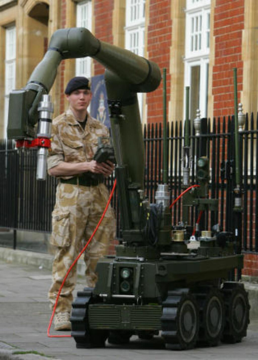 STOREBROR: Visekorporal Ben Miller viser frem den nye og større bomberoboten «Cutlass». Den vil neste år erstatte britenes gode gamle «trillebåren» som har vært i tjeneste siden 70-tallet. Foto: AFP/GEOFF CADDICK/SCANPIX