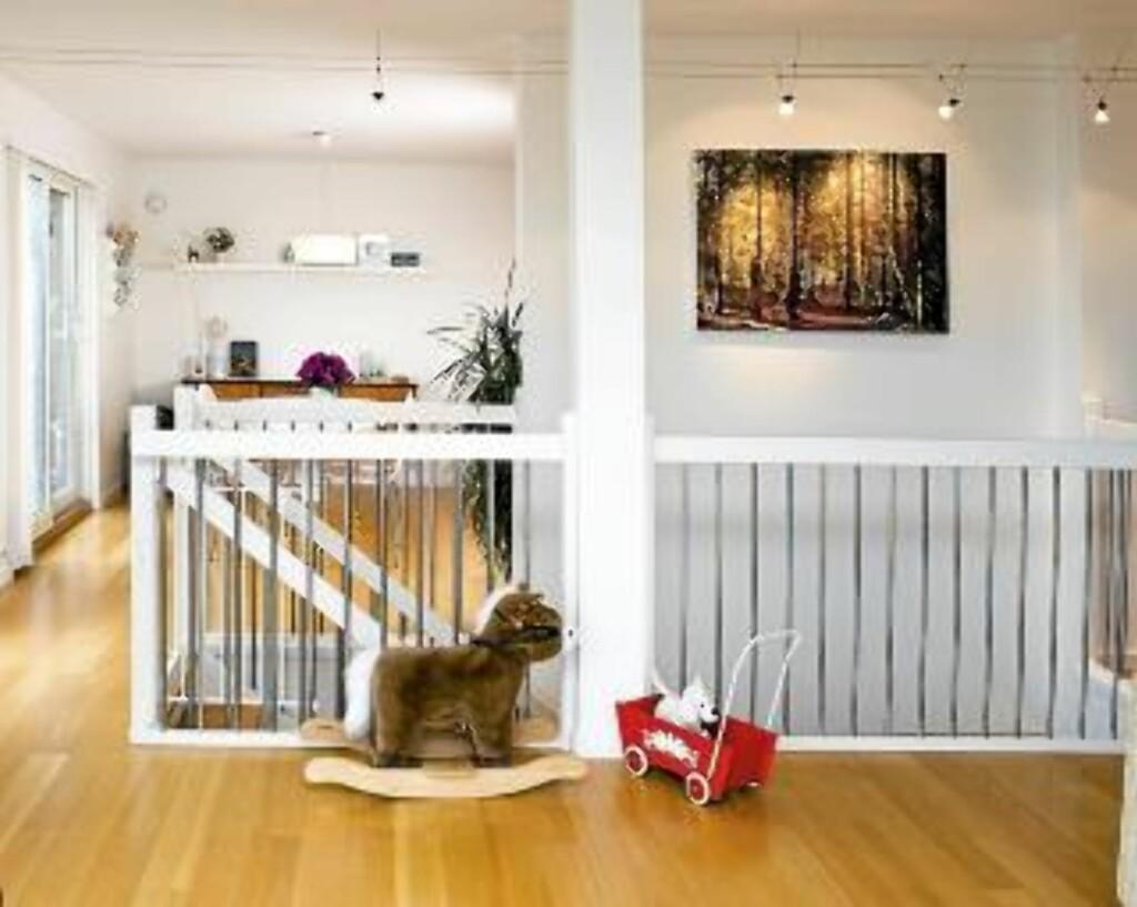 TILPASNINGER: Huset kom med eikeparkett og hvite vegger. På grunn av barna har Mette og Åsmund montert en grind fra Ikea foran den bratte trappen. Bildet på veggen er fra skogen utenfor huset, og er tatt av Mette. Foto: Bård Jørgensen