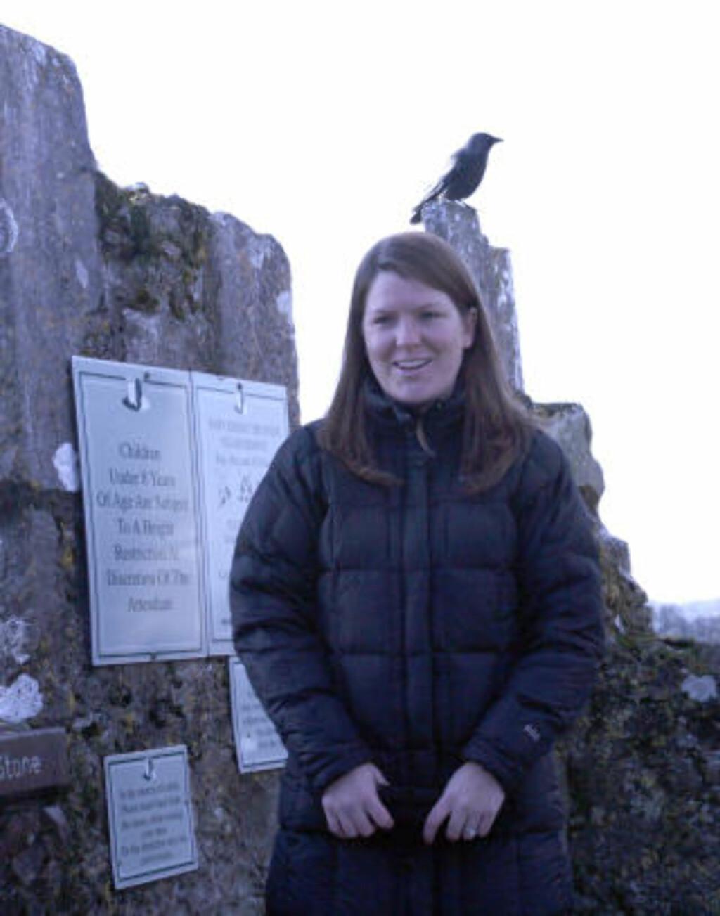 SKUMMELT: Med en ekte slottsravn i bakgrunnen, er kulissene om Blarney-steinen riktig skumle. Amerikanske Megan Yarbrough lot seg ikke skremme og kysset steinen, uten hemninger. Foto: Eivind Pedersen