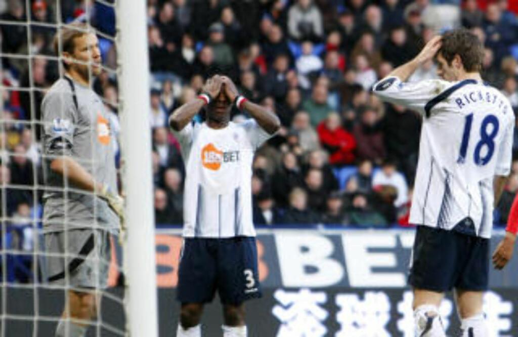FORTVILELSE: Boltons Jlloyd Samuel tar seg til topplokket etter å ha satt ballen i eget mål. Foto: AP Photo/Tim Hales